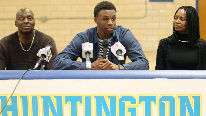 Huntington Prep basketball player Andrew Wiggins, center, flanked by his parents Mitchell Wiggins and Marita Payne-Wiggins, as he announces his commitment to the University of Kansas during a ceremony.