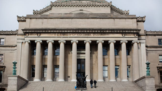 A man is dwarfed by the Columbia University Library as he sits outside the building in New York.