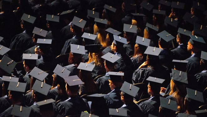 Students attend commencement ceremonies in the State Farm Center at the University of Illinois in Champaign May 12, 2013.