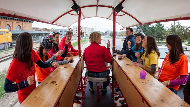 Sandy Theune, center, steers a 14-passenger quadracycle, Capitol Pedaler, with a group of three brides who are headed to a bar for their bridal shower in Madison, Wis.
