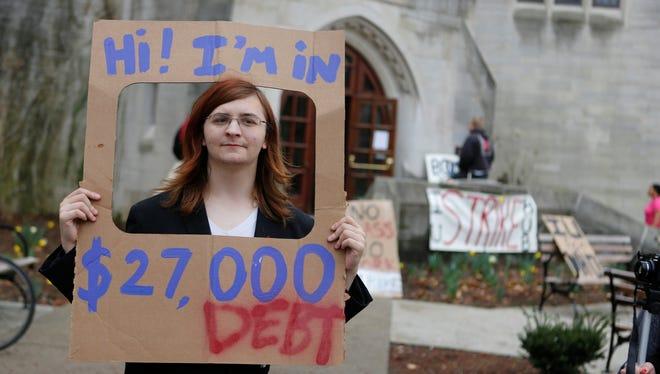 Indiana University senior Randall Burns holds a sign illustrating student debt.