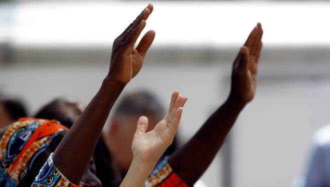 Participants raise their hands in praise during a National Day of Prayer event in Texas last year.