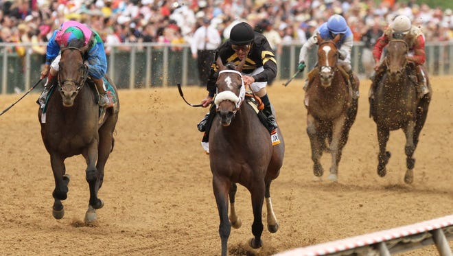 Gary Stevens aboard Oxbow leads down the final stretch as Joel Rosario aboard Orb, right, traisl behind at Pimlico. Orb finished fourth.