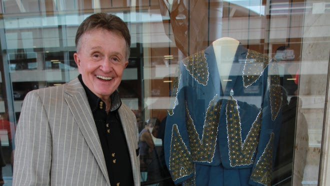 Bill Anderson, the performer and writer of country hits including 'Still' and 'The Tips of My Fingers,' poses by a display of one of his stage costumes at the new Nashville Songwriters Hall of Fame gallery.