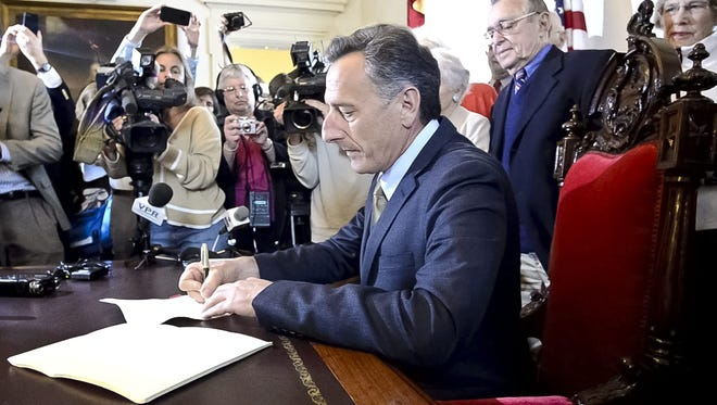 Vermont Gov. Peter Shumlin signs the end-of-life bill at the statehouse in Montpelier, Vt., on Monday, May 20, 2013. The law is the first to legalize physician-aided suicide by legislation.