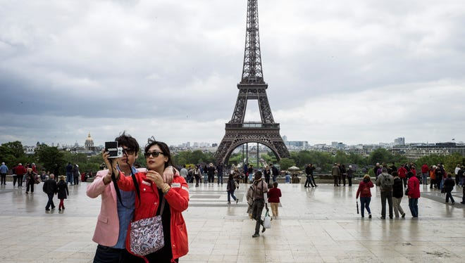 Tourists take a picture of the Eiffel Tower in Paris on May 14.
