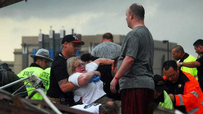 Emergency workers pull out a woman trapped in a building that was destroyed after a tornado ripped through Moore, Okla., on May 20.