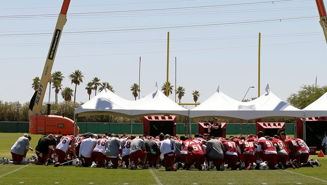 The Arizona Cardinals huddle to pray for the victims of the Oklahoma tornado before their NFL football organized team activities Tuesday in Tempe, Ariz.