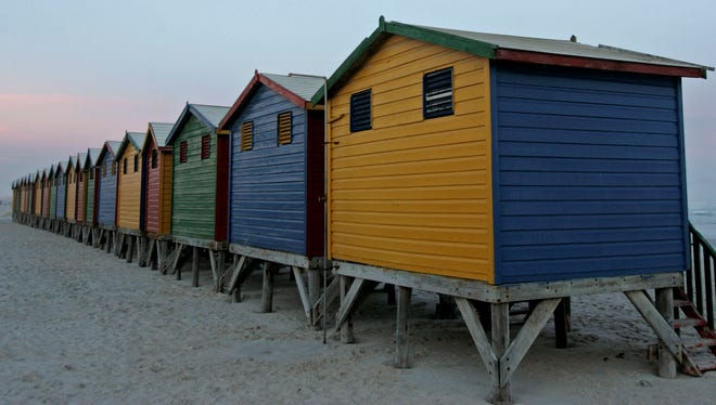 Multi-colored changing huts line the beach in Muizenberg, South Africa.