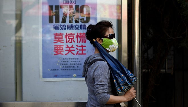 A woman wears a face mask April 24 as she walks past a poster showing how to avoid the H7N9 avian influenza virus in Beijing.