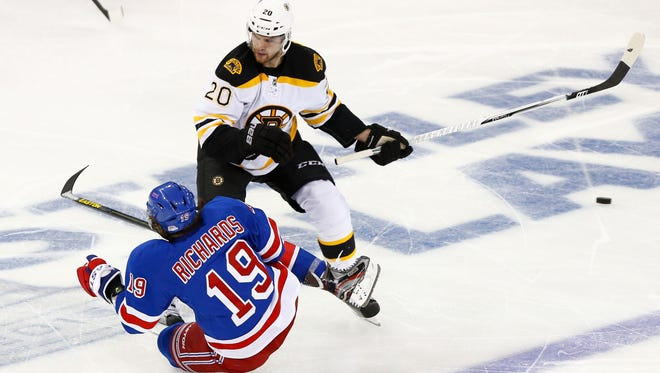 New York Rangers center Brad Richards falls in front of Boston Bruins left wing Daniel Paille in Game 3.