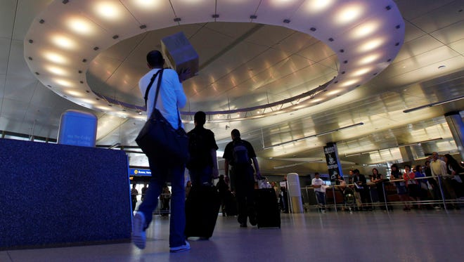 Arriving international passengers pass under a large 'halo' of light in the area where they meet friends and family at the Tom Bradley International Terminal at Los Angeles International Airport.