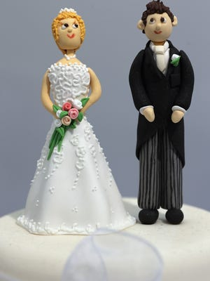 Bride and groom figurines are displayed on a cake during the National Wedding Show in London on Feb. 22, 2013.