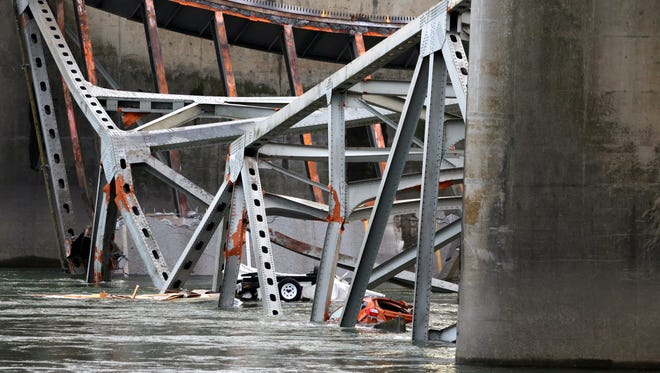 A car and travel trailer lie in the Skagit River with debris from the collapsed portion of the I-5 bridge in Washington state Friday.