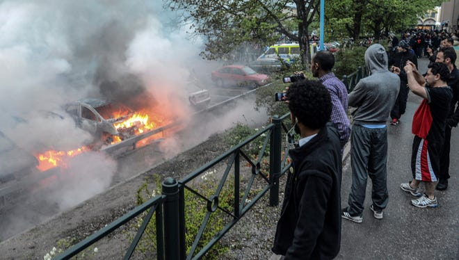 Bystanders take photos of a row of burning cars in the Stockholm suburb of Rinkeby after youths rioted in several different suburbs around the Swedish capital Thursday.