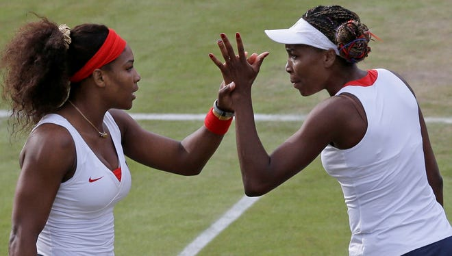 Serena Williams, left, and Venus Williams clasp hands as they compete in women's doubles at the 2012 Summer Olympics. The two are teaming up at the French Open for the first time in three years.