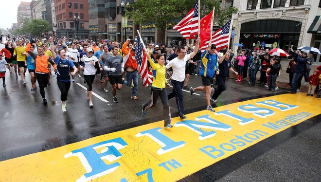 Runners who were unable to finish the Boston Marathon on April 15 because of the bombings cross the finish line after the city allowed them to finish the last mile of the race.