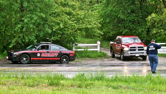 Police and firefighters search a wooded area in Ephratah, N.Y., on Saturday for a pilot of a small plane that crashed the day before.