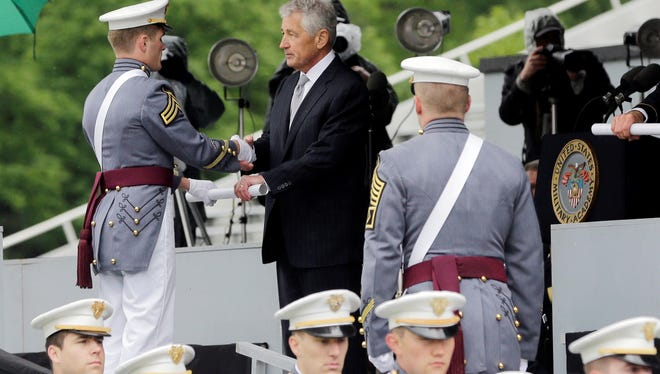 Defense Secretary Chuck Hagel hands diplomas to cadets during a graduation and commissioning ceremony at the U.S. Military Academy in West Point, N.Y. on Saturday, May 25, 2013.