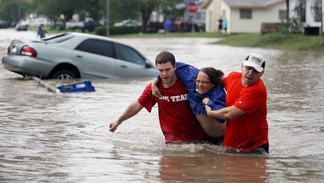 Marco Fairchild, left, and Gary Garza, right, help Sueann Schaller from her car Saturday, in San Antonio after she drove it into floodwaters.