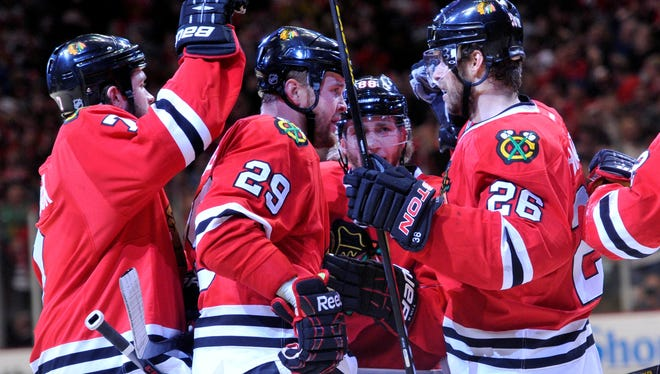 Blackhawks left wing Bryan Bickell (29) is congratulated by his teammates after opening the scoring against the Red Wings.