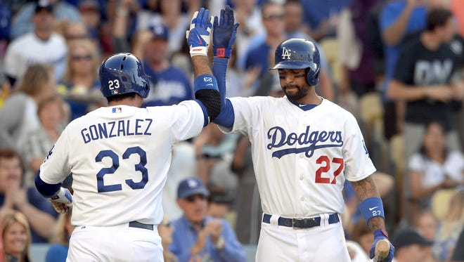 Los Angeles Dodgers first baseman Adrian Gonzalez heads to the dugout past Los Angeles Dodgers center fielder Matt Kemp after a solo home run in the fifth inning.