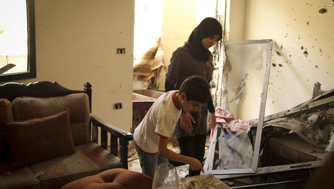 Residents in Hassan Hussein's second-floor apartment examine the aftermath of a rocket strike in a Shi'ite neighborhood in Beirut, Lebanon.