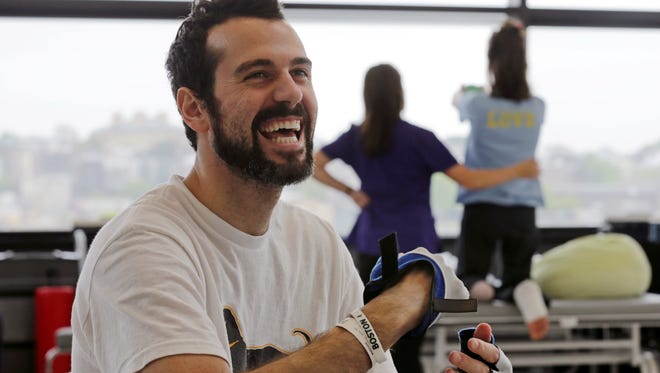 Pete DiMartino smiles through his physical therapy session at the Spaulding Rehabilitation Hospital in Boston on May 22.