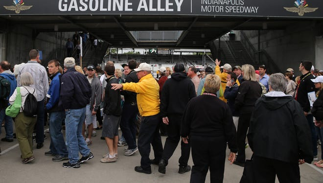 Yellow shirt security guards direct IndyCar fans through gasoline alley prior to the Indianapolis 500.