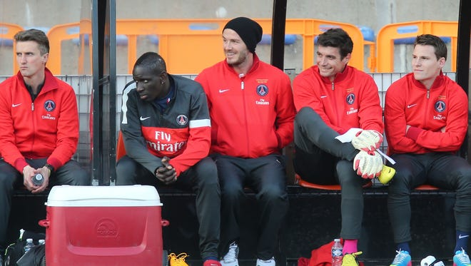 English midfielder David Beckham, second right, smiles with teammates on the Paris Saint Germain bench during his French League One soccer match against Lorient, Sunday, May 26, 2013 in Lorient, France.