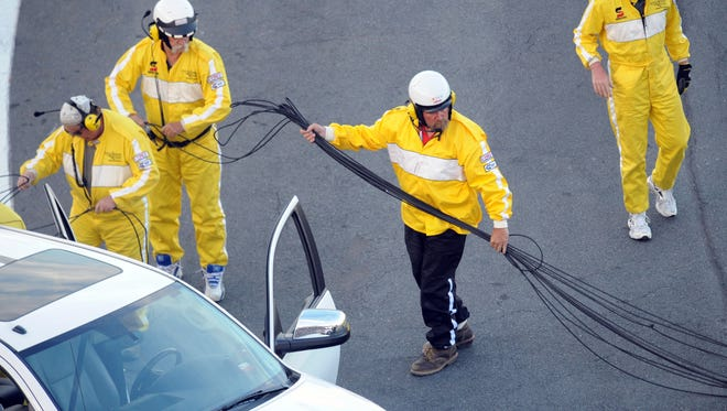 Safety workers retrieve a support cable for an overhead TV camera that broke during the Coca-Cola 600.