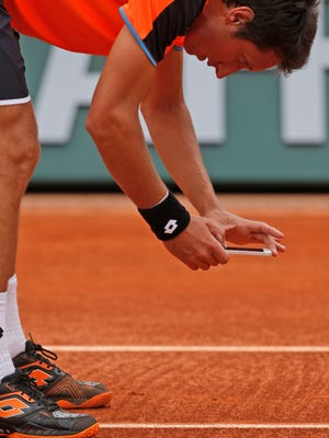 Sergiy Stakhovsky of Ukraine takes a picture of a mark after contesting the decision of the umpire. Stakhovsky didn't win the argument or the match, losing to Richard Gasquet.