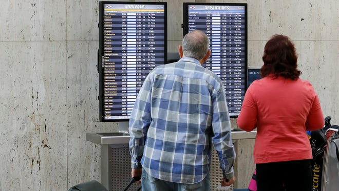 Travelers check flight status screens at Los Angeles International in April.