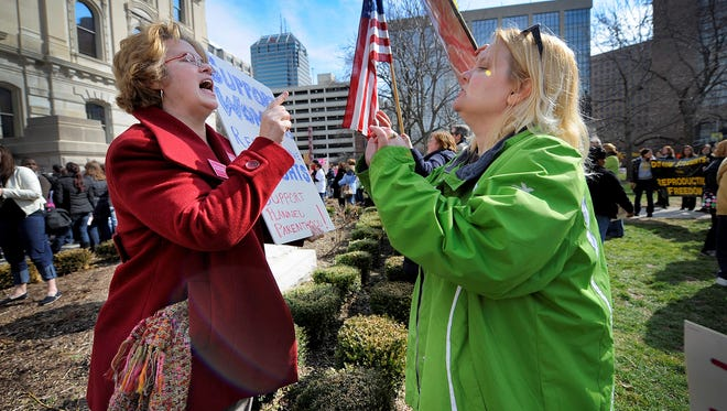 Planned Parenthood supporter Peg Paulson, left, and opponent Heather Pruett argue during a rally at the Indiana Statehouse in March 2011 about legislation that cuts off funding to Planned Parenthood because it provides abortions.