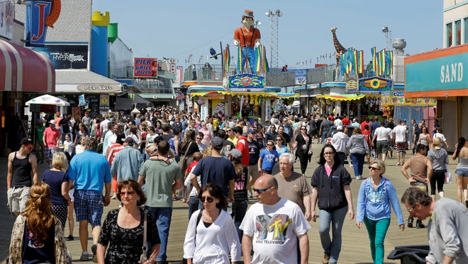 Large crowds of people walk along the newly rebuilt boardwalk in Seaside Heights, N.J., on Memorial Day.