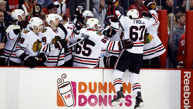 Chicago Blackhawks center Michael Frolik leaps at the bench after scoring on a penalty shot.