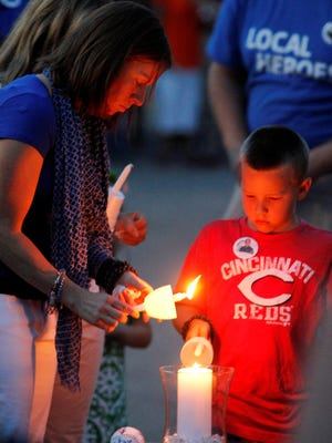 Amy Ellis, left, wife of slain Bardstown, Ky., police officer Jason Ellis, and his son Parker light candles during a vigil at the Bardstown Police Department.