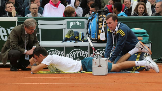 Australia's Bernard Tomic is treated for an injury in his first round match against Romania's Victor Hanescu at the French Open.
