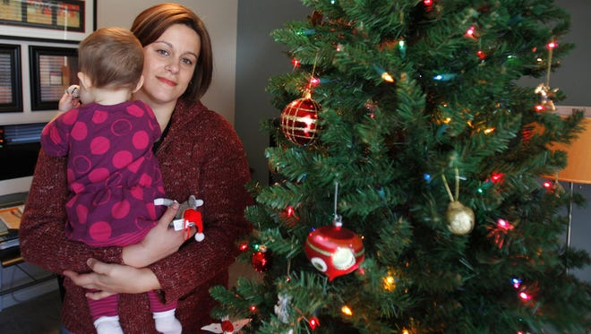 Christa Dias, holds her 11-month-old daughter in her Withamsville, Ohio, home in December 2011. She was a teacher at two Archdiocese of Cincinnati schools when she was fired.