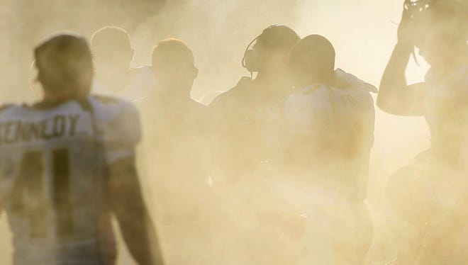 The Akron football team, shown here in a cooling mist early in its game at Florida International last season, is working to emerge from a fog of losing seasons.