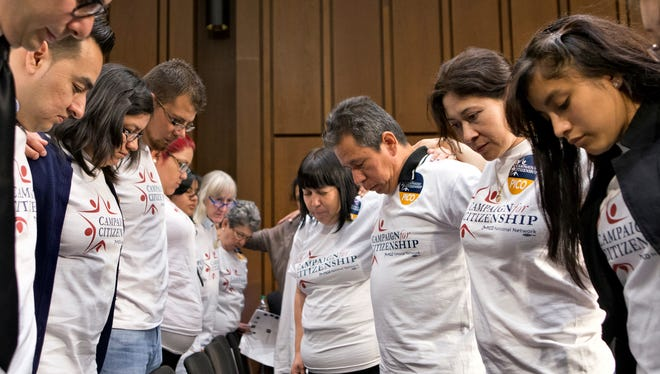 Immigration activists pray May 20 on Capitol Hill before the Senate Judiciary Committee began working on an immigration bill.