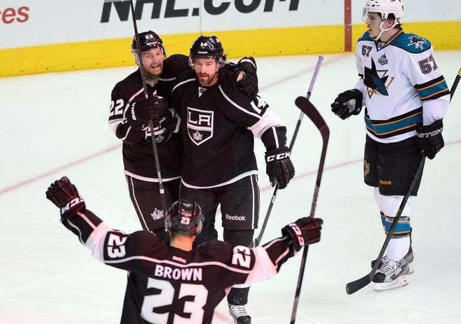 Los Angeles Kings right wing Justin Williams (14) celebrates with teammates Trevor Lewis (22) and Dustin Brown (23) after scoring a goal against the San Jose Sharks in the second period.