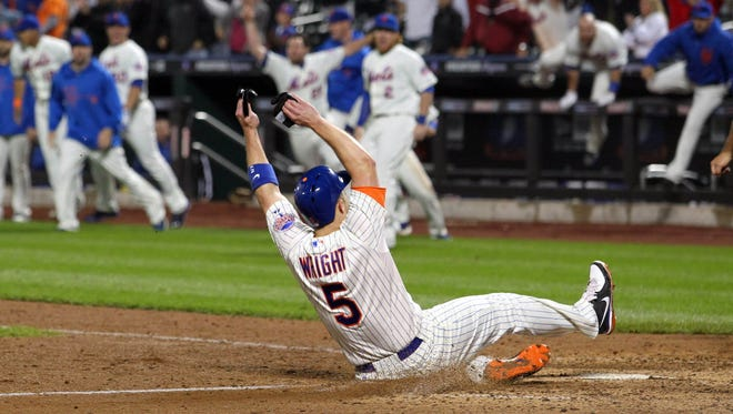 New York Mets third baseman David Wright (5) slides safely into home with the winning run during the bottom of the ninth inning of a game against the New York Yankees at Citi Field.