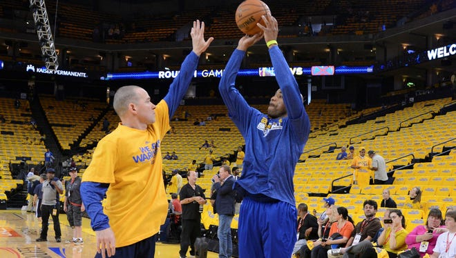 Golden State Warriors point guard Jarrett Jack (2, right) shoots the ball with assistant coach Michael Malone