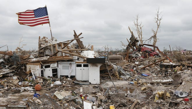 A flag flies amid the remains of tornado-destroyed homes in Moore, Okla.