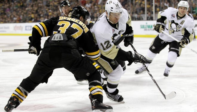 Penguins right wing Jarome Iginla (12), checked by Bruins center Patrice Bergeron, waived his no-trade clause to go to Pittsburgh.