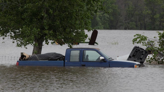 A truck sits partially submerged Tuesday in the Iowa River near a flooded home along Iowa 30 between Tama and Marshalltown