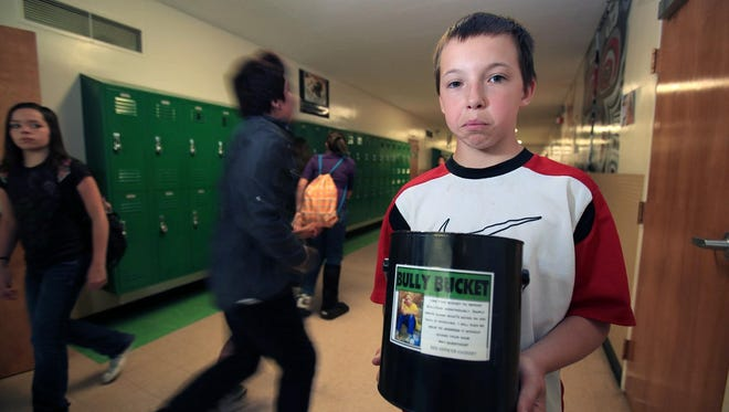 "Robert Stuart Middle School seventh-grader Austin Stearns pauses for a photo with the ""Bully Bucket in Twin Falls, Idaho. The school uses the bucket to combat bullying."