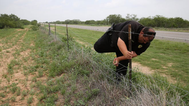Brooks County sheriff deputy Moe Saavdra climbs a fence searching for undocumented immigrants last week near Falfurrias, Texas.