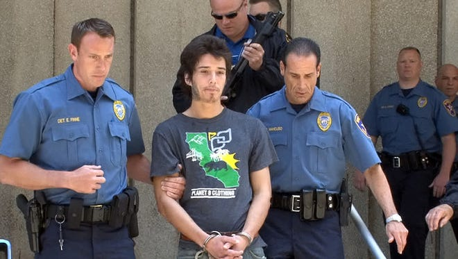 """Caleb McGillvary, also know as """"Kai the Hatchet-Wielding Hitchhiker"""" is escorted from the Union County Courthouse in Elizabeth, N.J., on Thursday, May 30, 2013. He is charged with the murder of 73-year-old lawyer Joseph Galfy."""